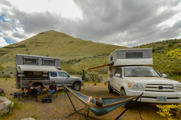 Trucks with slide in campers, dog, hammock, mountains, clouds, people