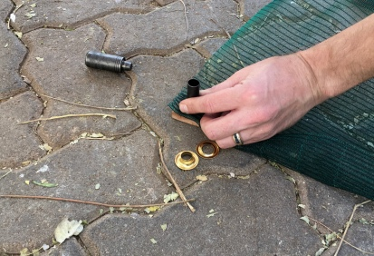 The tools supplied with the grommets both cut the material, and hammered the grommet in place.